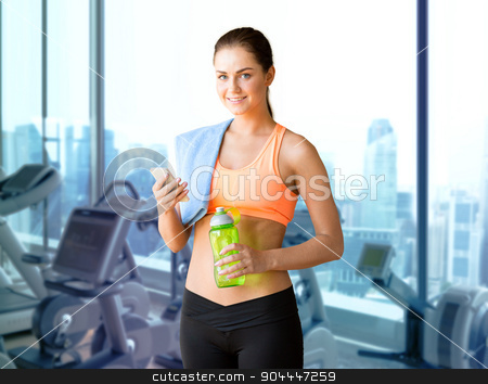 smiling sporty woman with smartphone in gym stock photo, sport, fitness, technology and people concept - smiling sporty woman with smartphone, bottle of water and towel over gym machines background by Syda Productions