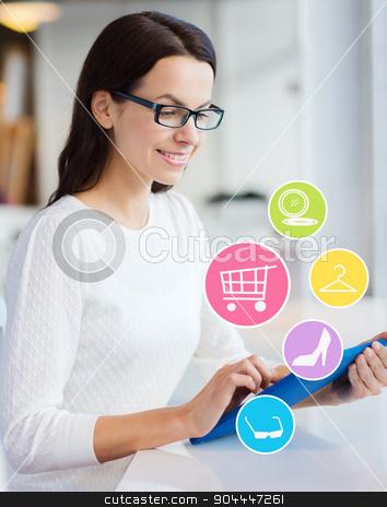 smiling woman with tablet pc shopping online stock photo, people, online shopping, technology and lifestyle concept - smiling young woman with tablet pc computer and internet icons at office or home by Syda Productions