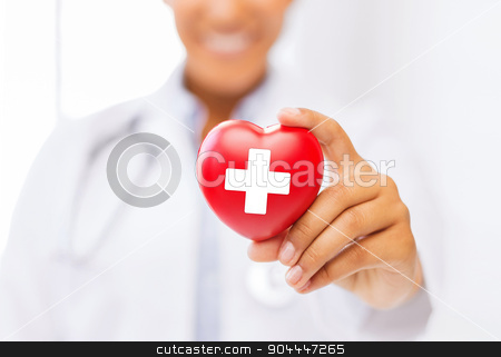 female doctor holding heart with red cross symbol stock photo, healthcare and medicine concept - female african american doctor holding heart with red cross symbol by Syda Productions