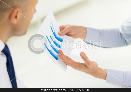 close up of businessman hands with chart stock photo, business, people, statistics and teamwork concept - close up of businessman hands showing chart to other man at office by Syda Productions