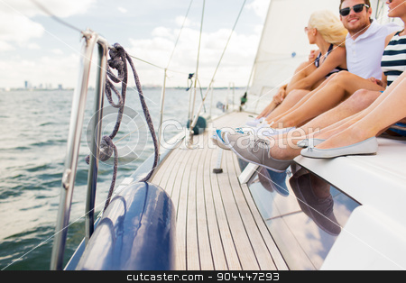 close up of friends legs sitting on yacht deck stock photo, vacation, travel, sea, sailing and people concept - close up of friends legs sitting on yacht deck by Syda Productions