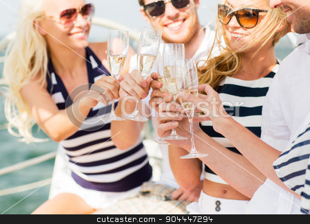 happy friends with glasses of champagne on yacht stock photo, vacation, travel, sea, holidays and people concept - close up of happy friends clinking glasses of champagne and sailing on yacht by Syda Productions