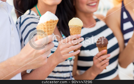 close up of happy friends eating ice cream stock photo, friendship, leisure, sweets, summer and people concept - close up of happy friends eating ice cream outdoors by Syda Productions