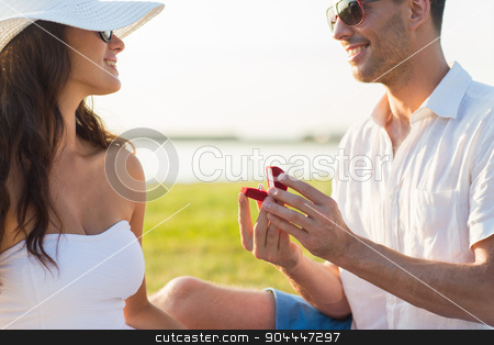 happy couple with engagement ring in gift box stock photo, love, proposal, people and holidays concept - happy couple with engagement ring in little red gift box by Syda Productions