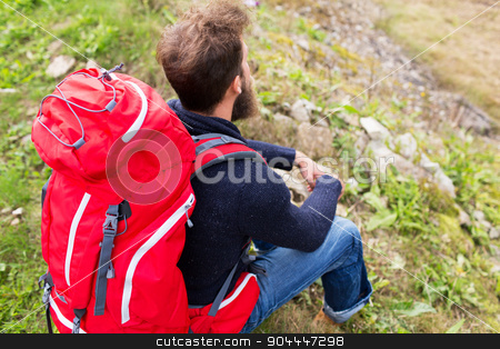 man hiker with red backpack sitting on ground stock photo, adventure, travel, tourism, hike and people concept - man hiker with red backpack sitting on ground by Syda Productions