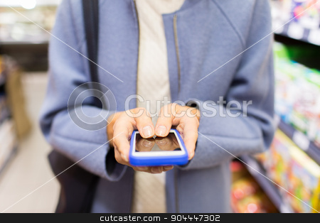 close up of woman with smartphone in market stock photo, sale, shopping, consumerism and people concept - close up of woman with smartphone choosing and buying food in market by Syda Productions