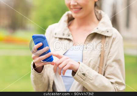 close up of woman calling on smartphone in park stock photo, drinks, leisure, technology and people concept - smiling woman calling or texting message on smartphone in park by Syda Productions