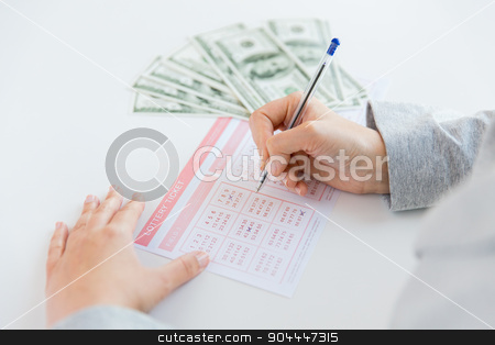 close up of hands with lottery ticket and money stock photo, business, finance, gambling and people concept - close up of woman hands filling lottery ticket and us dollar money by Syda Productions