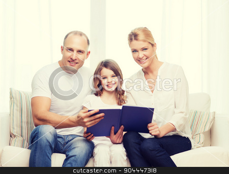 smiling parents and little girl with at home stock photo, family, child and home concept - smiling parents and little girl with book at home by Syda Productions