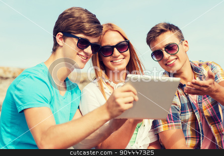 group of smiling friends with tablet pc outdoors stock photo, friendship, leisure, summer, technology and people concept - group of smiling friends with tablet pc computer sitting outdoors by Syda Productions