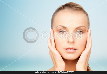 beautiful young woman touching her face stock photo, beauty, people and body care concept - beautiful young woman touching her face over blue background by Syda Productions