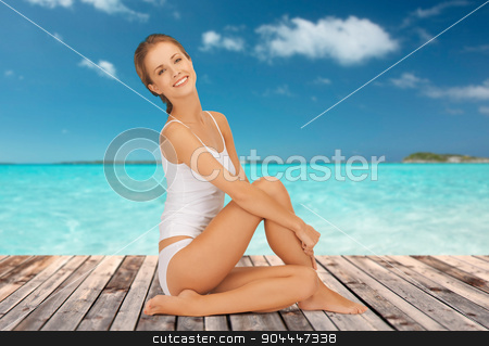 beautiful woman in cotton underwear stock photo, wellness, health and people concept - beautiful young woman in cotton underwear sitting on wooden floor over sea and blue sky background by Syda Productions