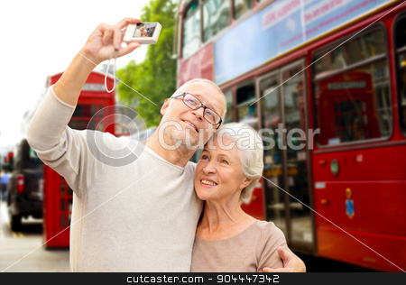 senior couple photographing on london city street stock photo, age, tourism, travel, technology and people concept - senior couple with camera taking selfie over london city street background by Syda Productions