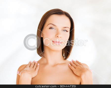 beautiful woman touching her shoulders stock photo, beauty, spa, health and people concept - beautiful woman touching her shoulders by Syda Productions