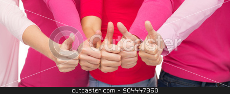 close up of women in pink shirts showing thumbs up stock photo, health care, people, gesture, breast cancer awareness and feminism concept - close up of women in pink shirts showing thumbs up by Syda Productions