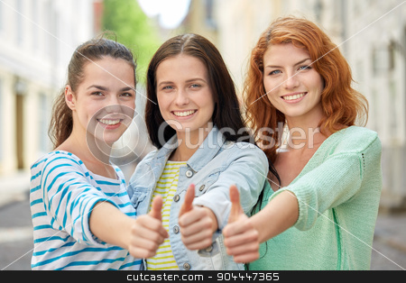 happy young women showing thumbs up on city street stock photo, vacation, weekend, leisure and friendship concept - smiling happy young women or teenage girls showing thumbs up on city street by Syda Productions