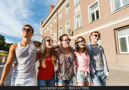 group of smiling friends walking in city stock photo, friendship, travel, tourism, summer vacation and people concept - group of smiling teenagers walking in city by Syda Productions