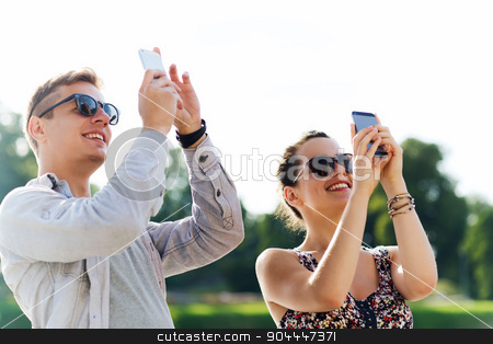 smiling friends with smartphone taking picture stock photo, friendship, leisure, summer, technology and people concept - group of smiling friends with smartphone taking picture outdoors by Syda Productions