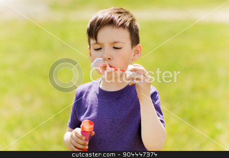 little boy blowing soap bubbles outdoors stock photo, summer, childhood, leisure and people concept - little boy blowing soap bubbles outdoors by Syda Productions