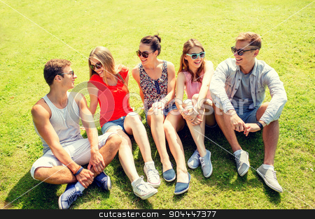 group of smiling friends outdoors sitting in park stock photo, friendship, leisure, summer and people concept - group of smiling friends outdoors sitting and talking on grass on grass in park by Syda Productions