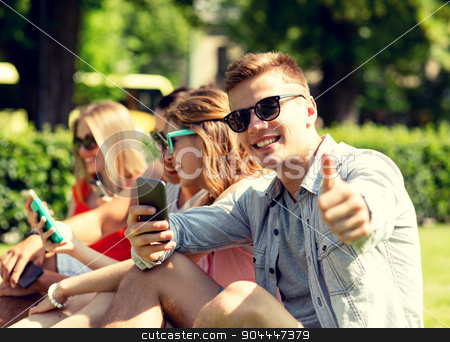 smiling man with smartphone showing thumbs up stock photo, friendship, leisure, technology and people concept - smiling man with smartphones showing thumbs up in front of his friends by Syda Productions