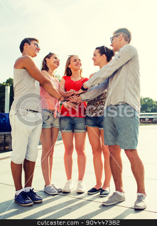 group of smiling friends with hands on top in city stock photo, friendship, leisure, summer, gesturer and people concept - group of smiling friends with hands on top in city by Syda Productions