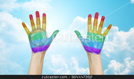 palms of human hands painted in rainbow colors stock photo, people, gay pride and homosexual concept - palms of human hands painted in rainbow colors over blue sky and clouds background by Syda Productions