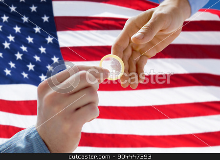 close up of male gay couple hands giving condom stock photo, people, homosexuality, safe sex, sexual education and charity concept - close up of male gay couple hands giving condom over american flag background by Syda Productions