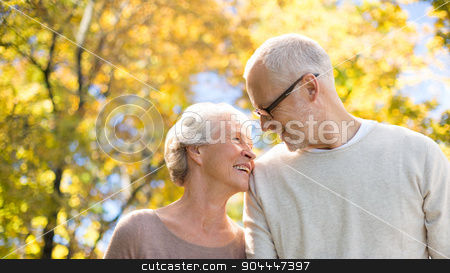 happy senior couple in autumn park stock photo, family, age, season and people concept - happy senior couple over autumn trees background by Syda Productions
