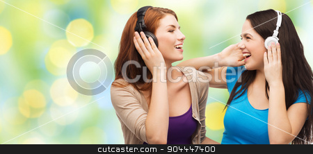 two happy girls with headphones listening to music stock photo, music and technology concept - two laughing teenage girls or young women with headphones listening to music over green lights background by Syda Productions