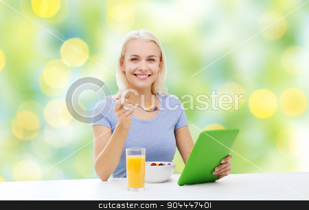 smiling woman with tablet pc eating breakfast stock photo, healthy eating, dieting and people concept - smiling young woman with tablet pc computer eating breakfast over summer green holidays lights background by Syda Productions