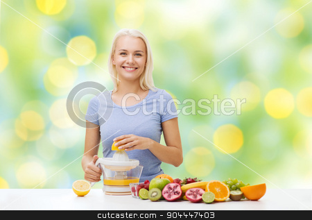 smiling woman squeezing fruit juice stock photo, healthy eating, vegetarian food, diet, detox and people concept - smiling woman with squeezer squeezing fruit juice over summer green holidays lights background by Syda Productions