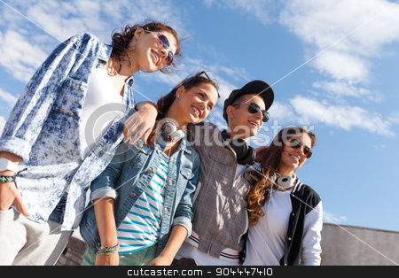 smiling teenagers in sunglasses hanging outside stock photo, summer holidays and teenage concept - group of smiling teenagers in sunglasses hanging outside by Syda Productions