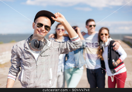 teenage boy with sunglasses and friends outside stock photo, summer holidays and teenage concept - teenage boy in sunglasses, cap and headphones hanging out with friends outside by Syda Productions