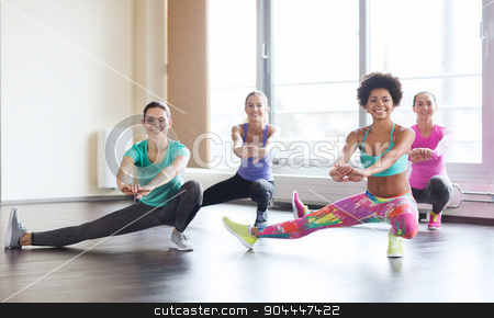 group of happy women working out in gym stock photo, fitness, sport, training, gym and lifestyle concept - group of happy women working out and stretching leg in gym by Syda Productions