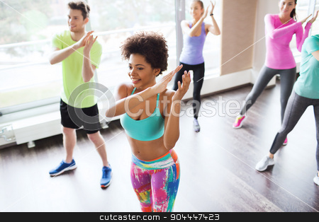 group of smiling people dancing in gym or studio stock photo, fitness, sport, dance and lifestyle concept - group of smiling people with coach dancing zumba in gym or studio by Syda Productions