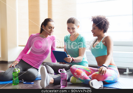 group of happy women with tablet pc in gym stock photo, fitness, sport, friendship, technology and lifestyle concept - group of happy women with tablet pc computer in gym by Syda Productions