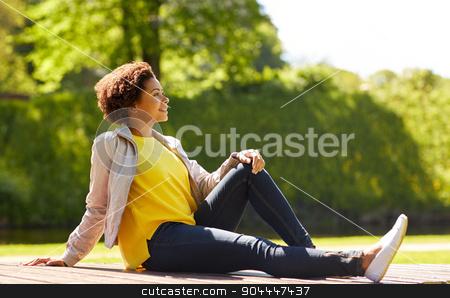 happy african american young woman in summer park stock photo, people, race, ethnicity and portrait concept - happy african american young woman in summer park by Syda Productions