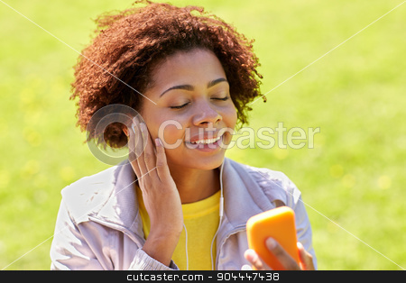 happy african woman with smartphone and earphones stock photo, technology, lifestyle and people concept - happy african american young woman or teenage girl with smartphone and earphones listening to music in summer park by Syda Productions