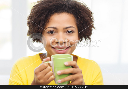 happy african american woman drinking from tea cup stock photo, people, drinks and leisure concept - happy african american woman drinking tea from cup or mug at home by Syda Productions