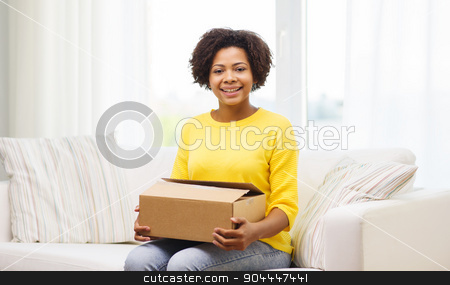 happy african young woman with parcel box at home stock photo, people, delivery, shipping and postal service concept - happy african american young woman holding open cardboard box or parcel at home by Syda Productions