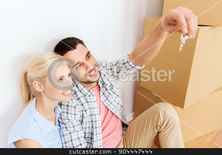 couple with key and boxes moving to new home stock photo, home, people and real estate concept - happy couple with key and cardboard boxes moving to new place by Syda Productions