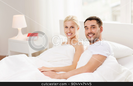 happy couple lying in bed at home stock photo, people, family, bedtime and happiness concept - happy couple lying in bed at home by Syda Productions