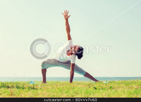 smiling man making yoga exercises outdoors stock photo, fitness, sport, people and lifestyle concept - smiling man making yoga exercises outdoors by Syda Productions