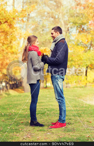 smiling couple with bunch of leaves in autumn park stock photo, love, relationship, family, season and people concept - smiling couple with bunch of leaves in autumn park by Syda Productions