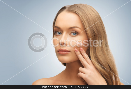 woman with pale and dark foundation tone on face stock photo, people, beauty, cosmetics and makeup concept - beautiful woman applying pale and dark foundation tone to face over gray background by Syda Productions