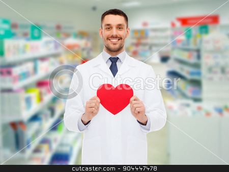 male pharmacist with heart at drugstore stock photo, medicine, pharmacy, people, health care and pharmacology concept - happy male pharmacist holding red heart shape over drugstore background by Syda Productions