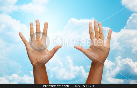 two african hands making high five over blue sky stock photo, gesture, people and body parts concept - african woman two hands showing palms or making high five over blue sky and clouds background by Syda Productions