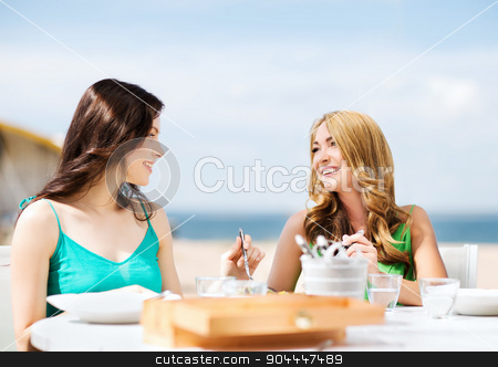 girls in cafe on the beach stock photo, summer holidays and vacation - girls in cafe on the beach by Syda Productions