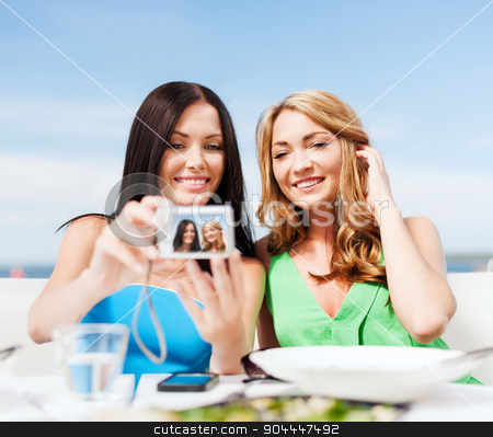 girls taking photo in cafe on the beach stock photo, summer holidays, vacation and technology - girls taking photo with digital camera in cafe on the beach by Syda Productions